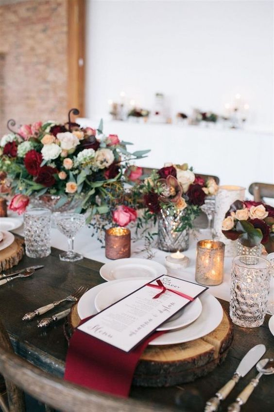 a winter wedding tablescape with a white runner, bold neutral and marsala blooms, greenery, wood slices and marsala napkins plus candles