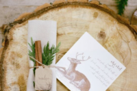 a wood slice instead of a usual placemat, a deer printed menu and cinnamon sticks and evergreens to mark the place setting