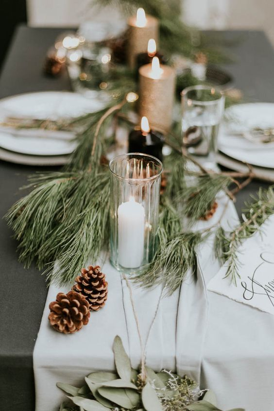an airy table runner with pine branches, pinecones and candles make the tablescape very chic and holiday-like