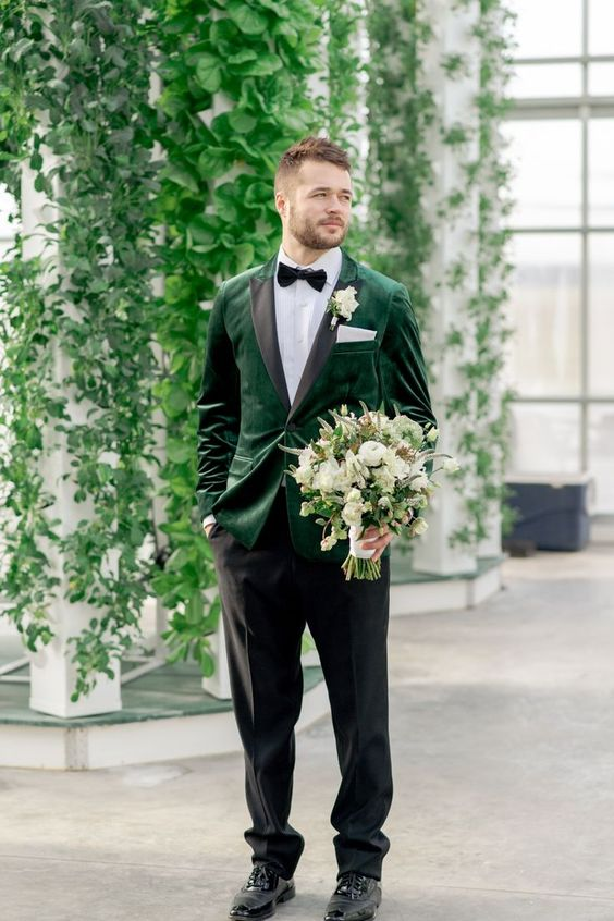 an elegant groom's look with an emerald velvet blazer with black lapels, a bow tie and black shoes