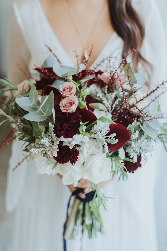 an ethereal winter wedding bouquet with marsala blooms, blush roses, pale greenery, twigs and some white blooms