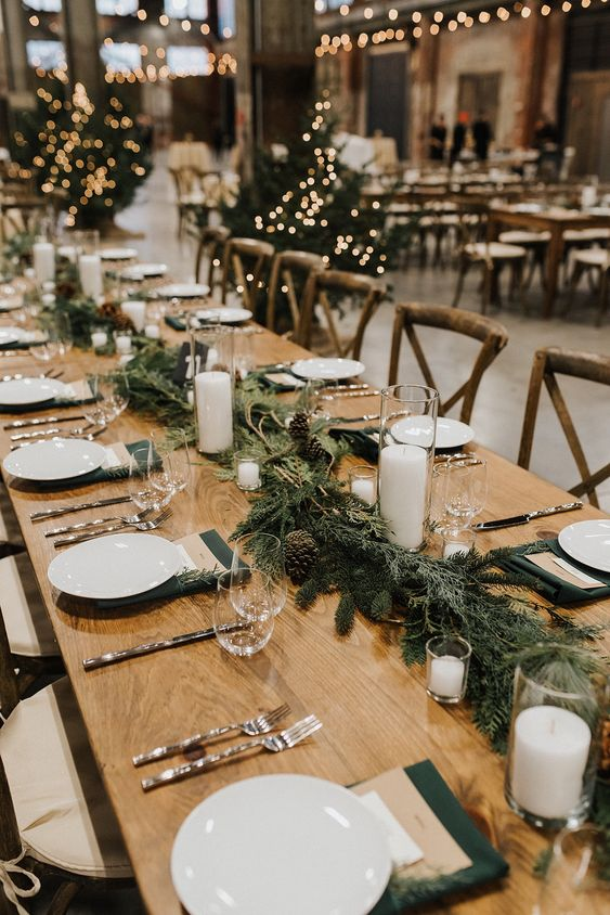 an evergreen and pinecone table garland with pillar candles is a lovely rustic decoration for a fall or winter wedding