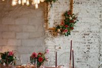 an exquisite wedding tablescape with a marsala tablecloth, candles, red and pink blooms and gold cutlery is amazing