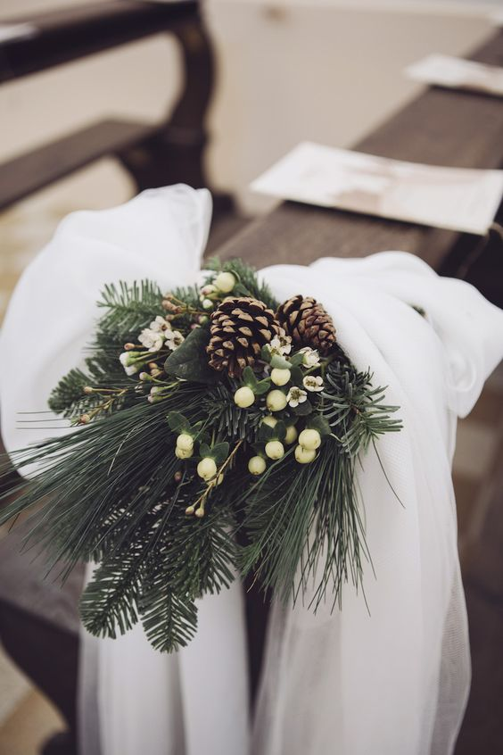 evergreens, pinecones, white blooms and berries plus lush white tulle for accenting your wedding aisle in a stylish way