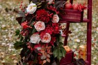 fall wedding decor in marsala colors – a ladder with boxes, fruits, leaves, marsala curtains with blush and red blooms and greenery