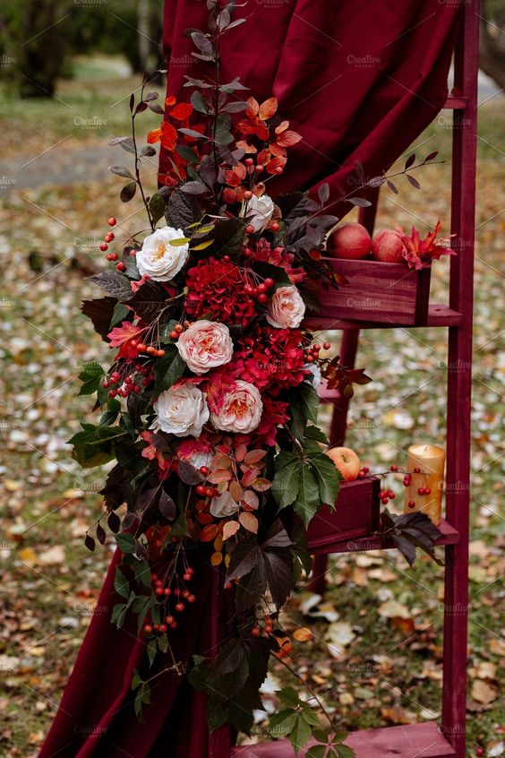fall wedding decor in marsala colors - a ladder with boxes, fruits, leaves, marsala curtains with blush and red blooms and greenery