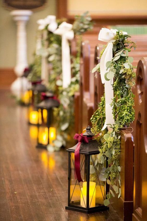 greenery and a white ribbon bow, a large candle lantern are ultimate to make your winer wedding aisle cozy and chic
