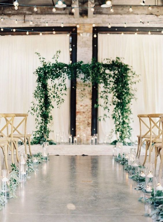 greenery and floating candles in tall vases and a greenery arch with candles create a very chic and natural ceremony space