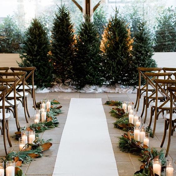 greenery and magnolia leaves garlands plus pillar candles will create really a festive feel in the ceremony space