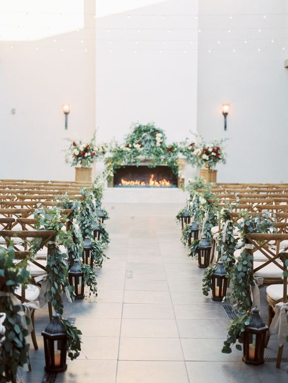 greenery chair posies and vintage dark candle lanterns make the ceremony space very chic and very natural