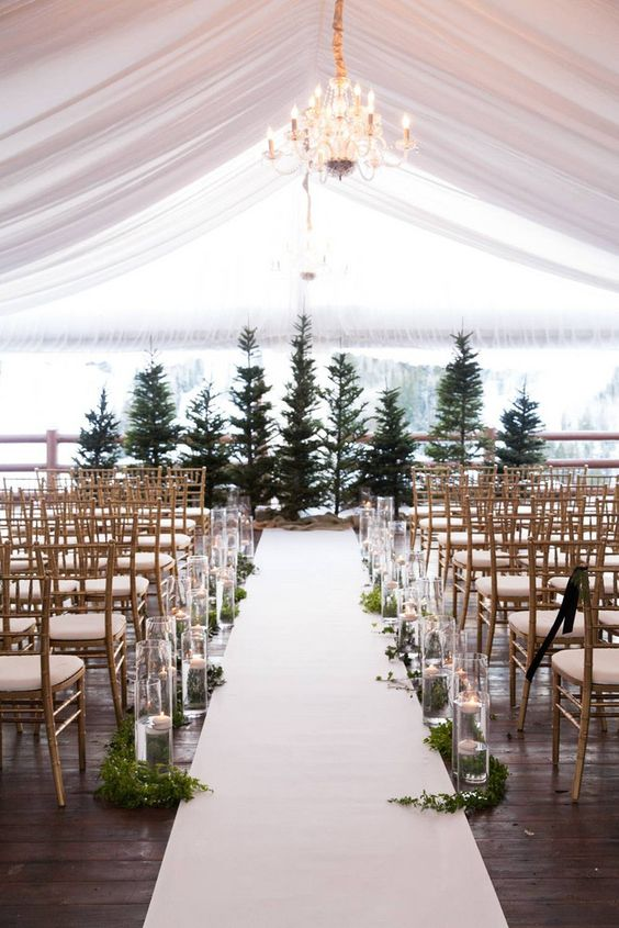 greenery, floating candles in tall vases help to create a winter wonderland feel in the ceremony space