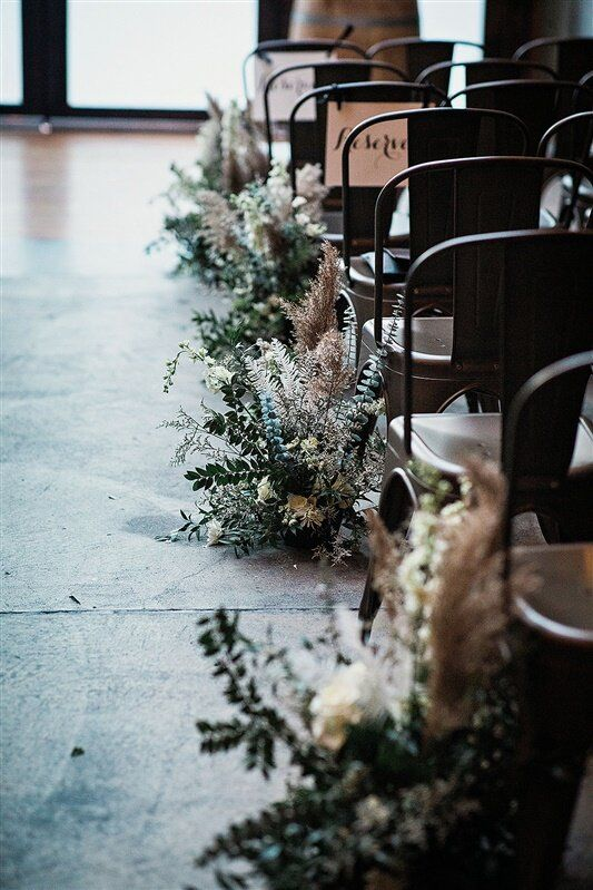 greenery, pampas grass and white blooms are very textural and chic arrangements to highlight your wedding aisle at its best