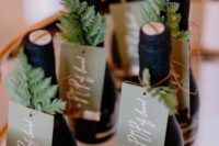 mini alcohol bottles topped with cards and evergreens will be nice and cool winter bridal shower favors