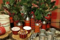 plaid thermoses are used as vases for antlers, evergreens and berries, plaid ribbons and plaid add winter charm