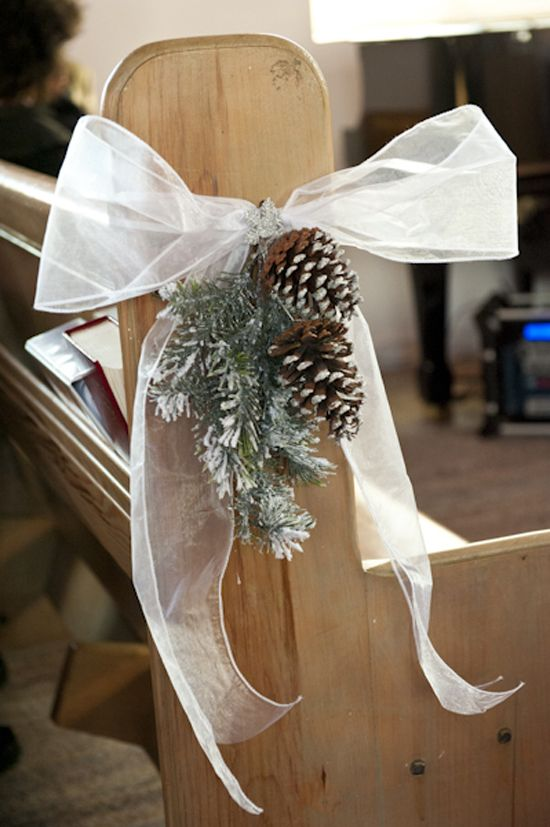 snowy evergreens, snowy pinecones and a large bow are traditional decorations for a winter wedding aisle