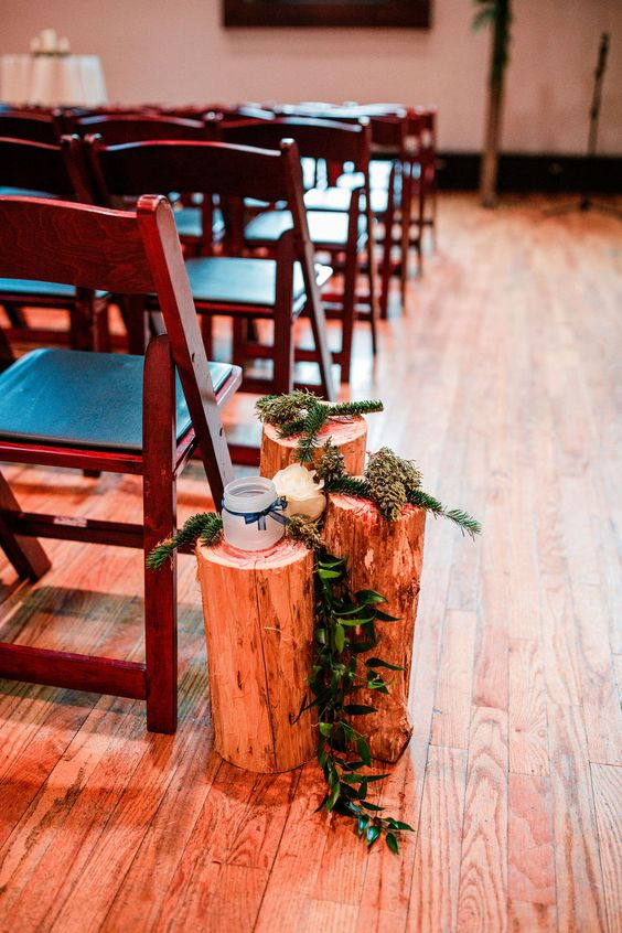 tree stumps with evergreens and cascading greenery and candle lanterns in jars make the aisle very natural and cool