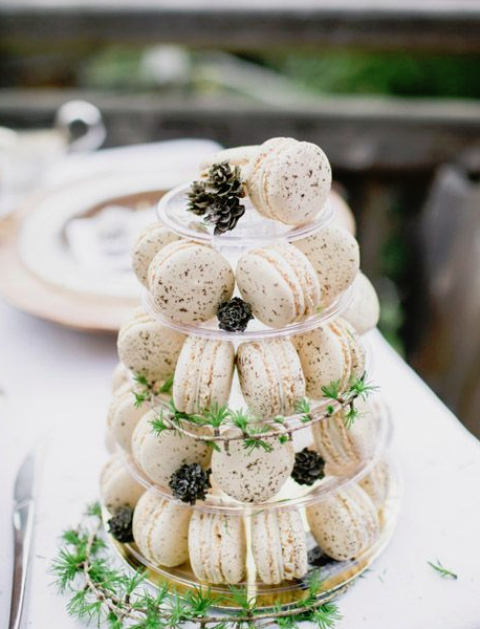 white macarons served on a stand with greenery and pinecones is a stylish winter-inspired idea