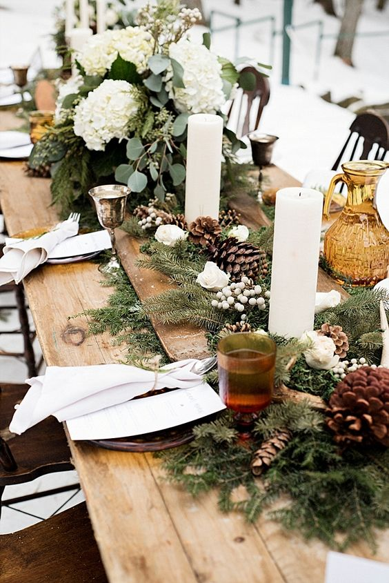 winter wedding table decor with evergreens, pinecones, white roses, berries, pillar candles and greenery