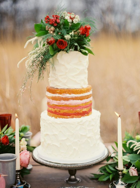 a Valentine wedding cake with a naked and buttercream tiers, greenery and white and red blooms
