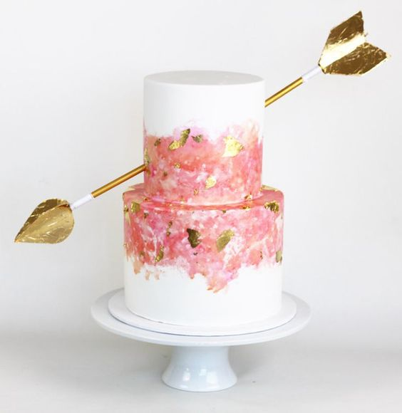a Valentine wedding cake with pink and gold leaf decor, with an oversized gold arrow is bold and cool