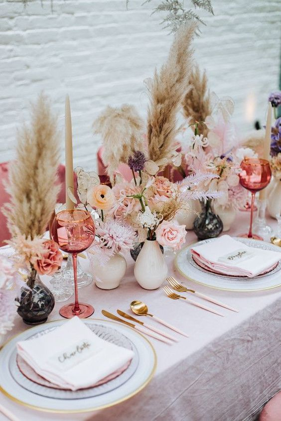a beautiful Valentine's Day wedding table in pink and blush, with pampas grass, white and black vases, stacked sheer and white plates and gold cutlery