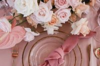 a beautiful Valentine's Day wedding table in pink, with gold rimmed plates, blush and pink blooms and a pink napkin