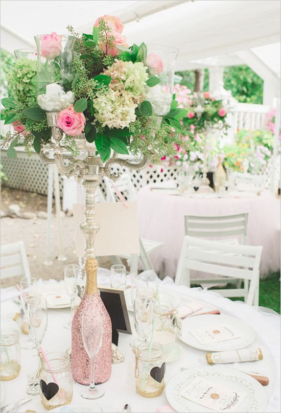a beautiful Valentine's Day wedding table with a pink glitter vase, a tall floral arrangement, jars with hearts and white porcelain