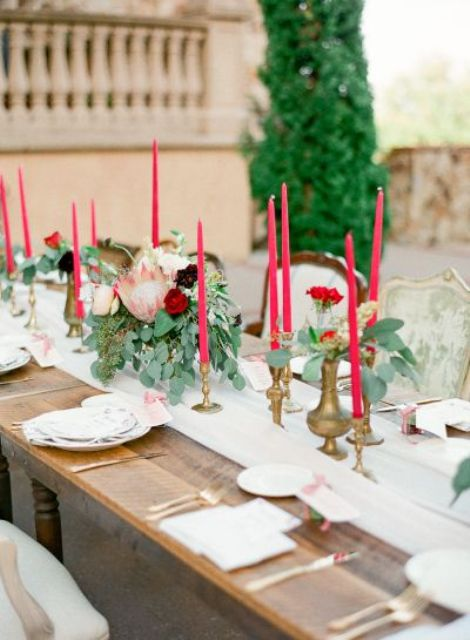 a beautiful Valentine's Day wedding tablescape with white linens, pink candles, greenery, printed and white plates is elegant