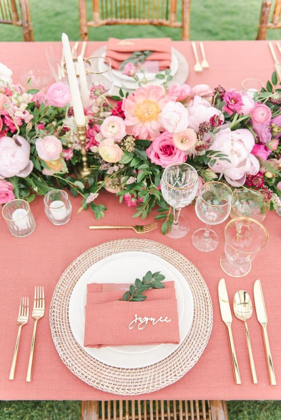 a beautiful Valentine's day wedding table in pink, with pink linens, bold pink blooms and white candles, gold rimmed glasses and gold cutlery