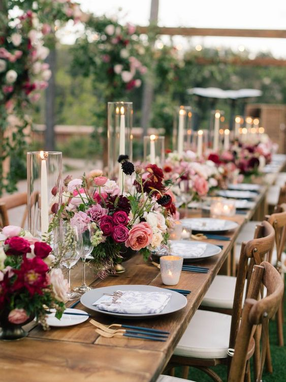 a beautiful and very romantic Valentine's Day wedding table with bold pink and burgundy blooms, candles, grey plates, navy and gold cutlery