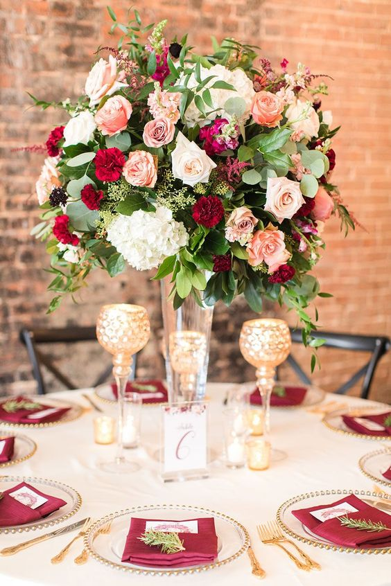 a beautiful floral centerpiece of burgundy, red, blush and white blooms and some greenery looks very chic