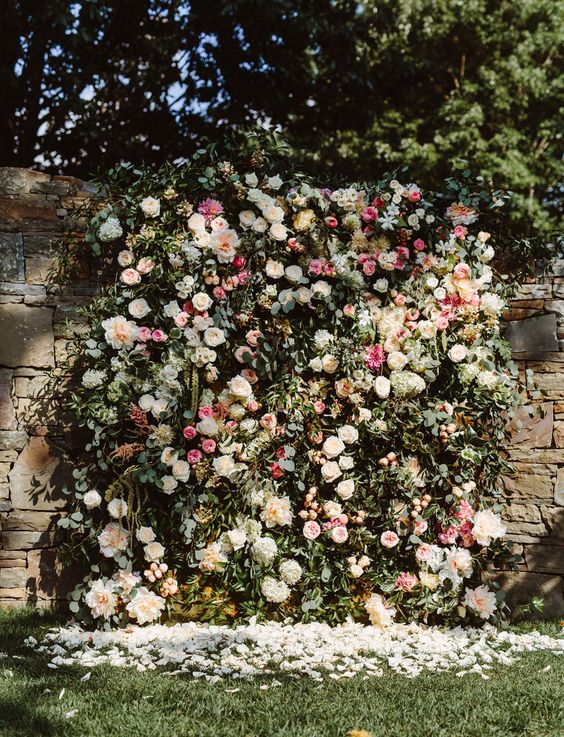 a beautiful lush floral wall with pink, blush and ivory blooms and textural greenery looks very lively