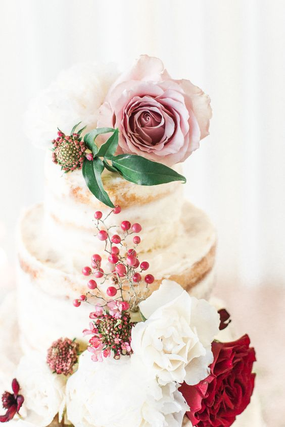 a beautiful naked wedding cake topped with berires, blush, white and red blooms and greenery is wow