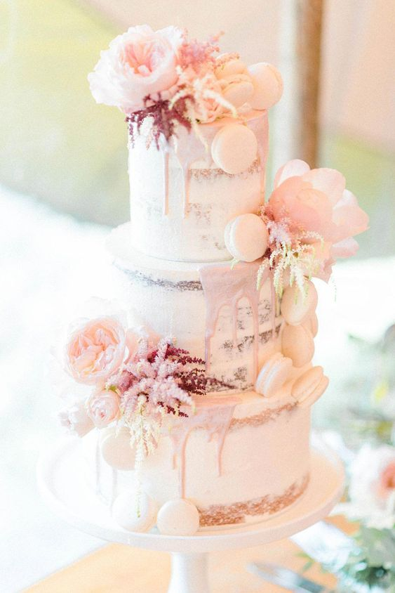 a beautiful naked wedding cake with blush drip, blush blooms and white macarons is a pretty and chic idea