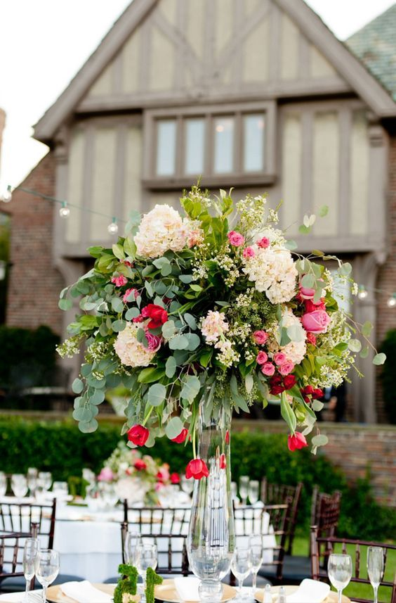 a beautiful oversized wedding centerpiece of white, pink and red blooms and lots of greenery for Valentine's Day