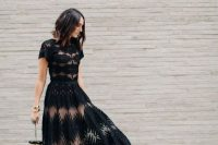 a black lace maxi dress with an A-line skirt, a high neckline, short sleeves, a quirky bag and embellished shoes