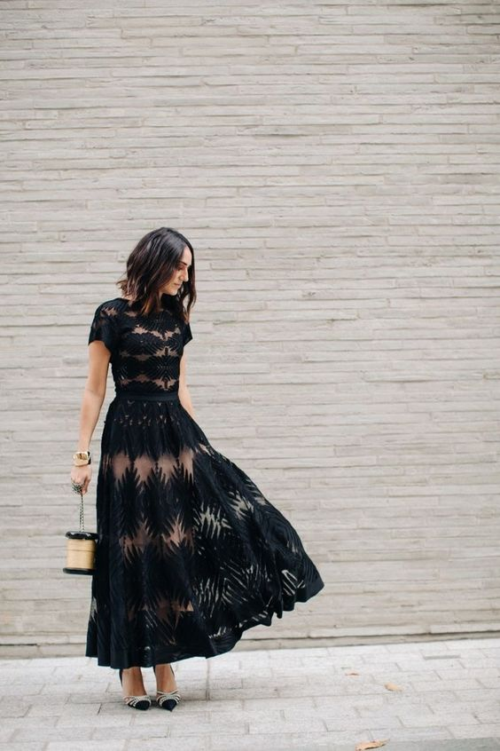 a black lace maxi dress with an A line skirt, a high neckline, short sleeves, a quirky bag and embellished shoes