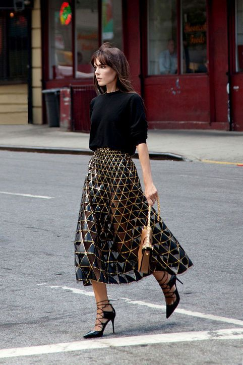 a black oversized top, a black and gold geometric midi skirt, black strappy shoes and a brown bag