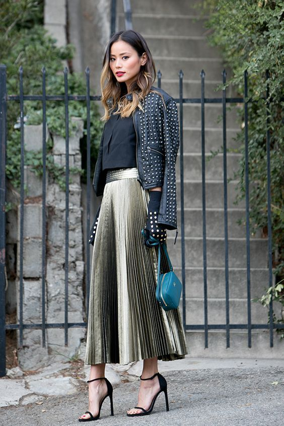 a black shirt, a metallic pleated midi skirt, a black studded jacket, black shoes and a teal bag