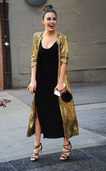 a black slip midi dress with a side slit, black strappy shoes, a shiny gold duster and a black bag