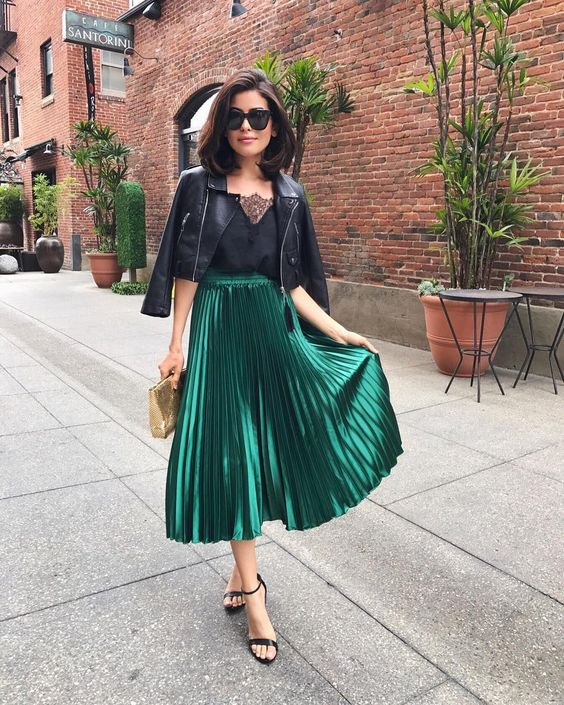a black top with a lace neckline, a black cropped leather jacket, a green metallic pleated midi skirt, black heels
