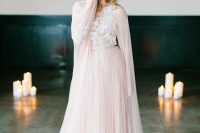 a blush A-line wedding dress with a lace bodice, a pleated skirt and a matching capelet is a chic and beautiful idea