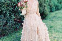 a blush A-line wedding dress with floral appliques and plunging neckline plus a front slit for a romantic bride