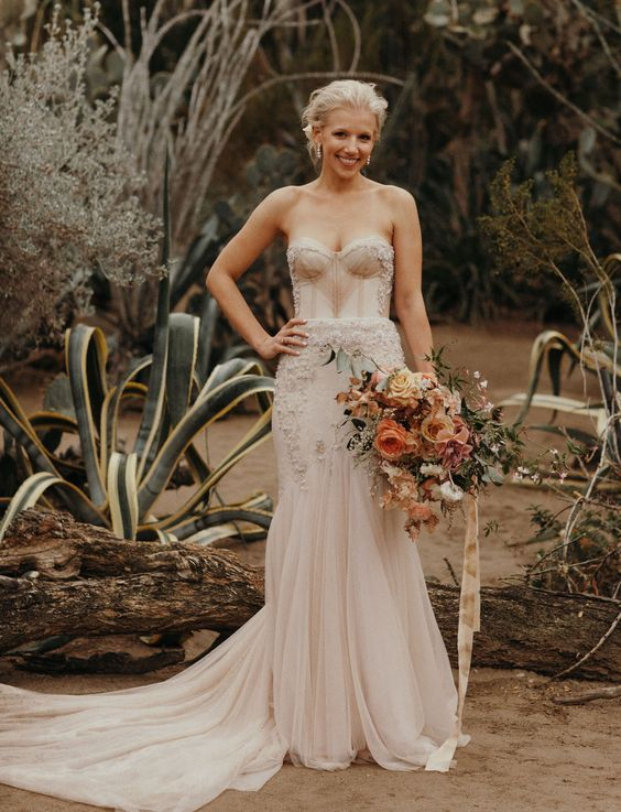 a blush mermaid wedding gown with a strapless sweetheart neckline and a pleated skirt, a train and embroidery and embellishments