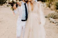 a blush tulle wedding dress with a plunging neckline and embroidery for a stunning outfit at a Valentine's Day wedding