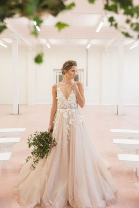a blush tulle wedding dress with floral appliques on the bodice and a deep V-neckline