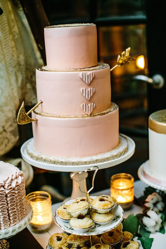 a blush wedding cake decorated with gold glitter and a gold arrow for a Valentine wedding with a soft color scheme