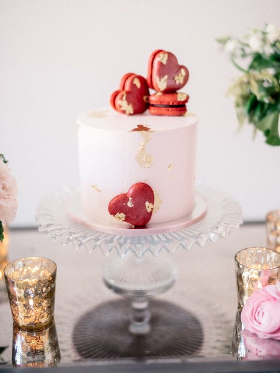 a blush wedding cake decorated with gold leaf and red heart-shaped macarons is a cool idea for a Valentine wedding