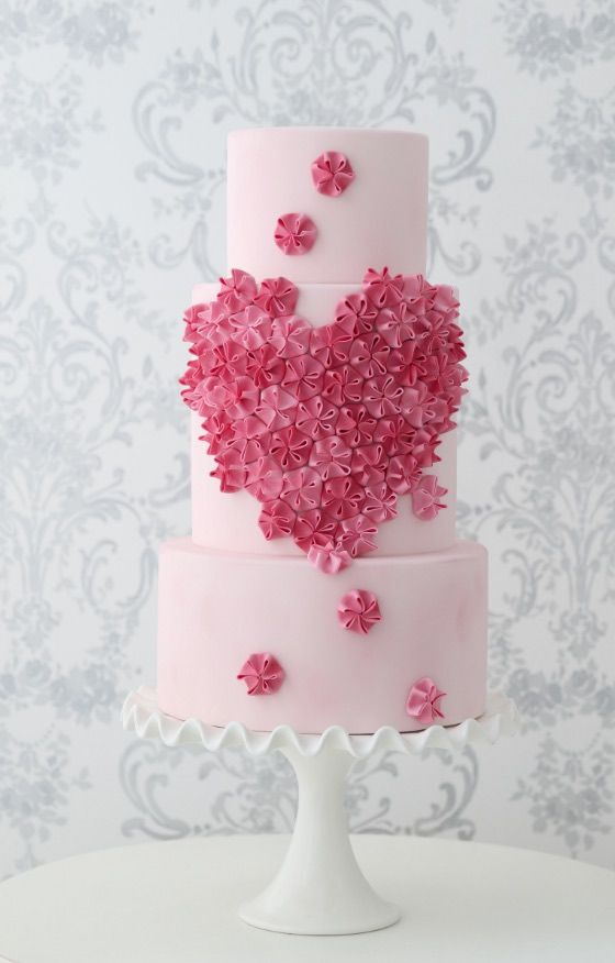 a blush wedding cake decorated with pink and light pink cream blooms looks very romantic and very chic