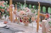 a blush wedding tablescape with candles, blooms, greenery, white porcelain, white linens and silver cutlery is very romantic